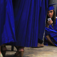 Aaliyah Hurley, a Tupelo High School graduating senior, looks up from her phone as she waits backstage with her classmates for the graduation ceremony to start.
