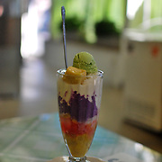 Halo halo, a Filipino dessert with shaved ice and coconut milk along with a mixture of ingredients such as jackfruit, young coconut, sweet beans, ube (purpla yam), and agar agar. Topped with ice cream and leche flan, the diner mixes everything together before eating.
