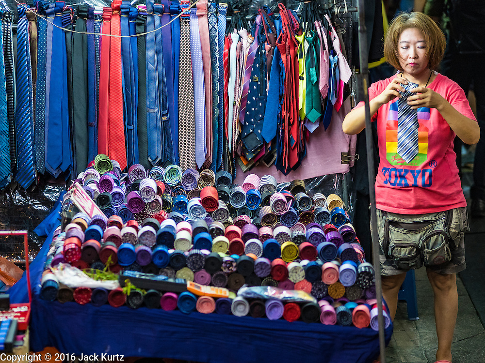 26 MAY 2016 - BANGKOK, THAILAND: A woman who sells neck ties in the Silom Road night market sets out her merchandise and waits for customers. The night market on Silom Road, close to Bangkok's famous Patpong tourist area, is being closed by the Bangkok municipal government. Vendors have been told they have to leave the sidewalk on Silom Road by the end of May, 2016. The market is the latest street market being shut down by city officials as a part of the government's plan to clean up Bangkok. The Silom Road night market sells mostly tourist oriented clothes, inexpensive Thai art, and bootleg movies on DVD.       PHOTO BY JACK KURTZ