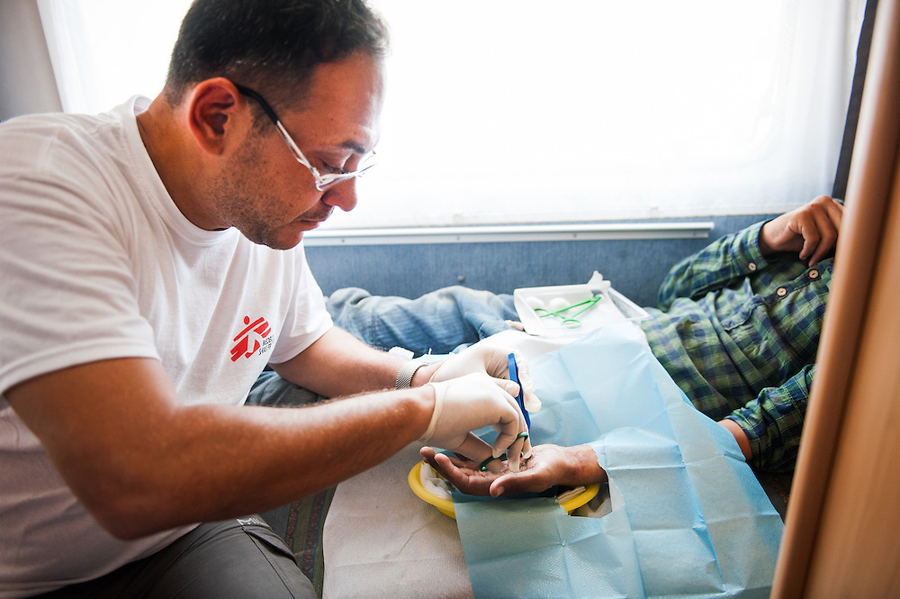 Dimitri Giannoulis the MSF doctor at the mobile unit at the port of Mytiline treats an Afghan teenager who burned his left hand at a forest fire in Turkey.