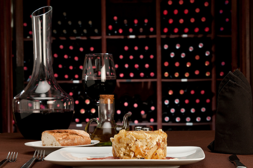 """Restaurante table setting with  tapa huevos rotos, literally translated as """"broken eggs"""", is a Spanish staple dish of potatoes, ham and eggs. Wine cellar in the background"""