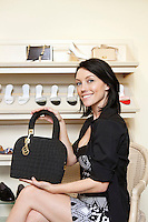 Portrait of a happy mid adult woman showing designer purse in shoe store