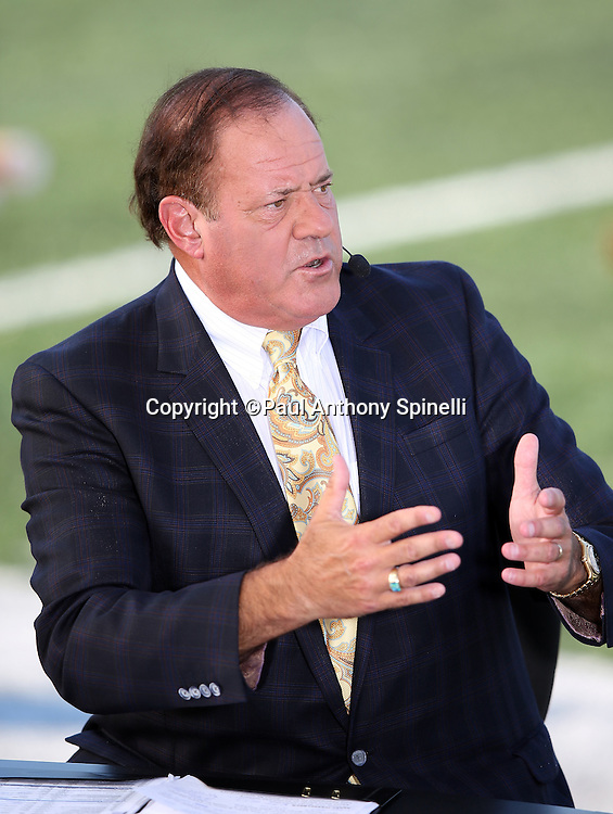 ESPN television sports analyst Chris Berman does commentary on a field level broadcast booth before the Green Bay Packers 2016 NFL Pro Football Hall of Fame preseason football game against the Indianapolis Colts on Sunday, Aug. 7, 2016 in Canton, Ohio. The game was canceled for player safety reasons due to the condition of the paint on the turf field. (©Paul Anthony Spinelli)