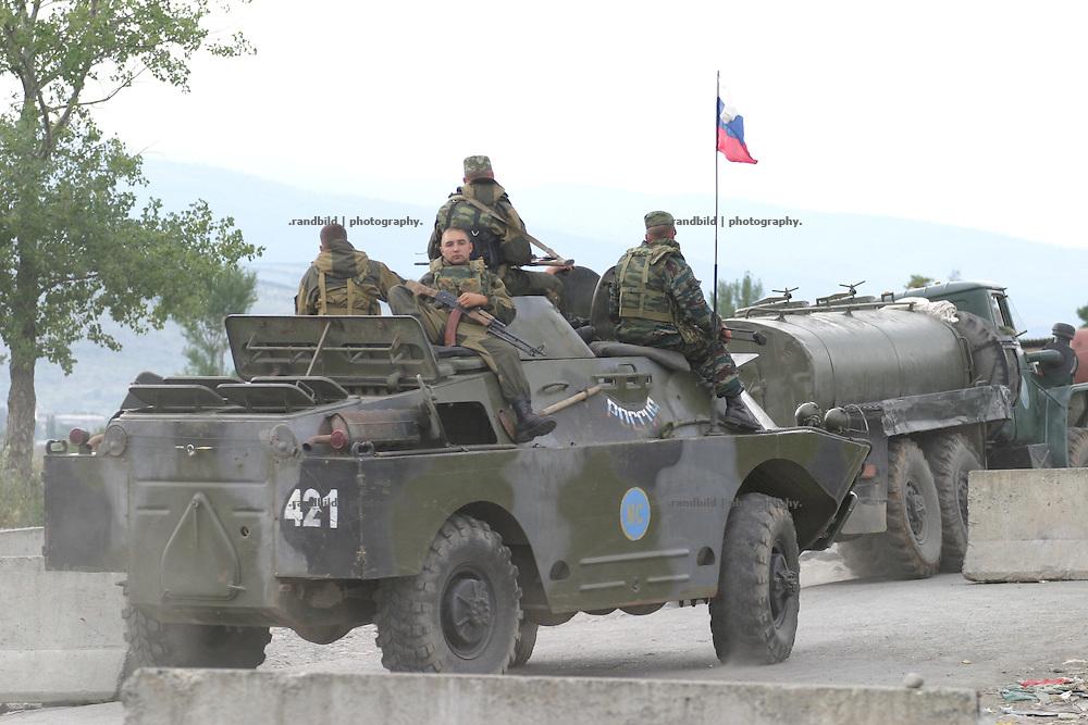 Ein russicher Militarkonvoi passiert einen georgischen Checkpoint. Ein Checkpoint georgischer Truppen an der Grenze zur international nicht anerkannten Republik Süd-Ossetien. Als die Sowjetunion Anfang der 1990er zerfiel, erklärte sich Süd-Ossetien unabhängig und spalte sich von Georgien ab. Den anschliessenden Krieg gewannen die Süd-Osseten. Seit dem kommt es immer wieder zu bewaffneten und unbewaffneten Zwischenfällen. A russian military convoi is crossing a georgian checkpoint. A checkpoint of the georgian military at the borderline of the unrecognized Republic of South-Ossetia. During the breakdown of the Sowjet-Union South-Ossetia split off Geogia and declared itself as independent. They won the following war between them and Georgia. South-Ossetia is an international unrecognized state.