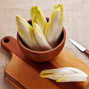 whole chicory in wooden bowl on a wooden board with knife.