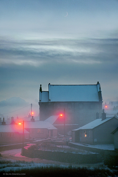 Aberffraw church in the main village, in mist at dusk, during a particularly cold, snowy winter