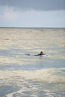 Surfer paddling out in sea