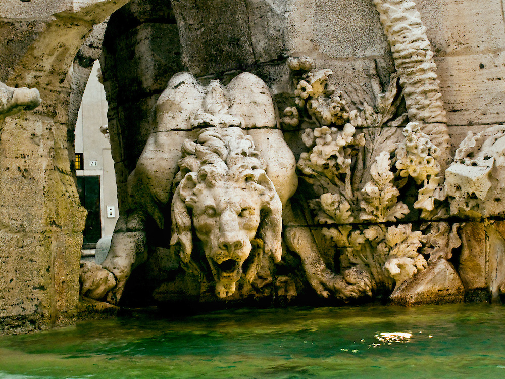 Piazza Navona; Bernini's Fountain of the Four Rivers, detail of the lion lapping the water at the base of the fountain.