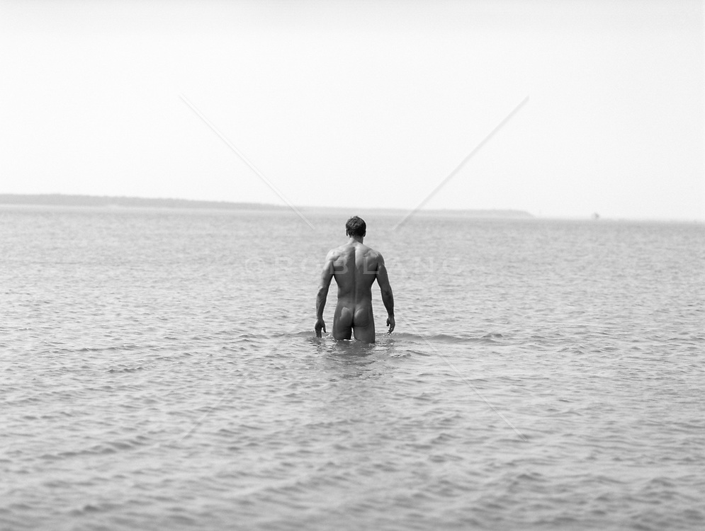 nude man walking in the water during low tide