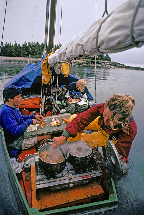 MAINE COAST, SAILING, ATLANTIC, Family cooking meals aboard  gaf rigged pulling boat