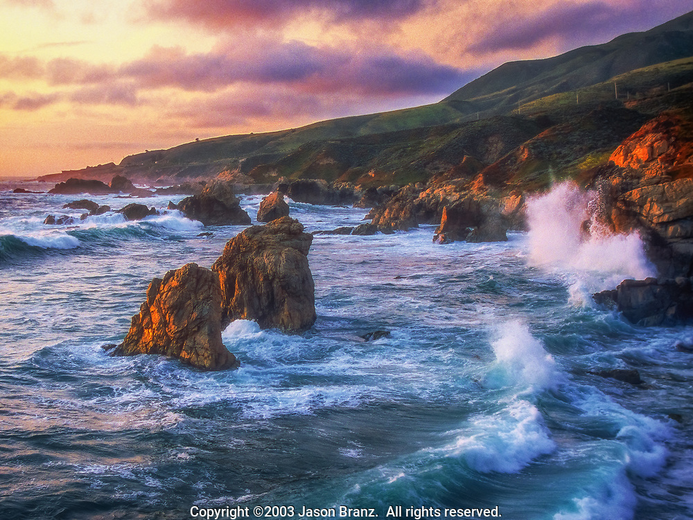 Crashing waves, sea stacks, and low marine clouds at sunset along the Big Sur Coast, California.