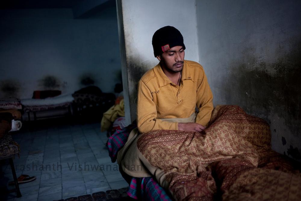 "Iellyas Masih, 23 sits on his bed, at ""Navjeevan"" drug rehabilitation center in Amritsar, India, on Wednesday, December 15, 2010. Photographer: Prashanth Vishwanathan/HELSINGIN SANOMAT"