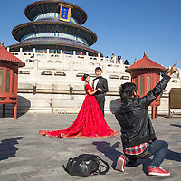 China, Beijing, Photographer directs young couple posing for wedding portraits outside Hall of Prayer for Good Harvest at Temple of Heaven Park on sunny autumn afternoon