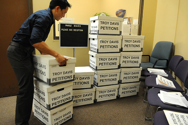 ATLANTA, Georgia - September 15, 2011: Kung Li organizes boxes containing more than 600,000 signatures in support of clemency for death-row inmate Troy Davis in the reception area of the Georgia Board of Pardons and Paroles at the James &quot;Sloppy&quot; Floyd Building in Atlanta.<br /> <br /> Death-penalty opponents and civil rights leaders this morning delivered more than 600,000 petition signatures to the state Board of Pardons and Paroles asking officials to grant clemency to Troy Davis, the long-time death-row inmate who's maintained he didn't kill Savannah police officer Mark MacPhail more than 20 years ago. More than 40,000 signatures were collected in Georgia.<br /> <br /> According to Amnesty International, a human rights group which has helped raise awareness about Davis' case, nine individuals have signed affidavits implicating another man for the officer's killing...&quot;Mark MacPhail is a hero and we grieve for his mother and family,&quot; the NAACP's Edward DuBose said at a morning news conference. But &quot;too many people have come forward and said Troy Davis did not kill MacPhail.&quot;<br /> <br /> The five-member Georgia Board of Pardons and Paroles, which meets Monday, is most likely the last hope for Davis, who's scheduled to be executed on Sept. 21. A majority vote by the board will decide whether Davis' sentence is commuted or if his execution will proceed.