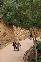 Two old ladies walk along the path between Park Guell and the former home, now museum, of Antoni Gaudi in Barcelona, Spain.