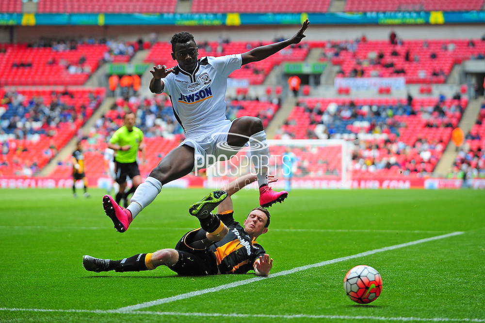 Mustapha Bundu of Hereford FC hurdles the tackle of Stephen Forster  of Morpeth Town AFC during the FA Vase match between Hereford FC and Morpeth Town at Wembley Stadium, London, England on 22 May 2016. Photo by Mike Sheridan.
