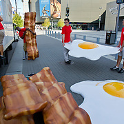Oversized strips of foam bacon and sunny-side-up eggs were shuttled into a trailer from the entrance of the Sprint Center Tuesday morning by (from left to right) Becky McGee, Craig Moore II, Josh Houk and Ben McCarthy, who were working for GMR Marketing in an ad campaign for Wendy's new breakfast menu. The faux food has been accompanied by coupons and coffee for curious pedestrians.
