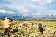 Photographers capturing the Grand Tetons in Grand Teton National Park.  This is one of my favorite vantage points in the park because of the curvy buck rail fence