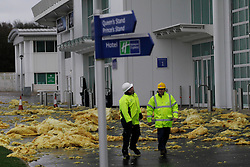 © Licensed to London News Pictures. 03/01/2012, London, UK. Two workers walk through roof insulation materials from the wind damaged grandstand roof of Epsom Down race course in south London as stormy weather hit part of UK, Tuesday, Jan. 3, 2012. Photo credit : Sang Tan/LNP