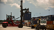Ship to shore cranes load container ship, and trucks haul containers at the Georgia Ports Authority's Port of Savannah, Monday, July 10, 2017, in Garden City, Ga.  (GPA Photo/Stephen B. Morton)