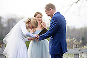 Annapolis, Maryland - April 18, 2015: Stephanie Shearer Cate is having a hard time slipping Winston Bao Lord's wedding ring on his finger during their wedding at the home of Jeff and Marry Zients' house in Annapolis, Maryland Saturday April 18, 2015. Hannah North, background, Stephanie's lifelong friend leads the  exchange of vows.<br /> <br /> <br /> <br /> CREDIT: Matt Roth for The New York Times<br /> Assignment ID: 30173318A