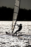 Backlighting creates a dramatic image of a windsurfer on Lake Calhoun in Minneapolis, MN.