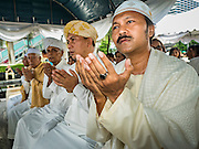 21 AUGUST 2015 - BANGKOK, THAILAND: Muslim Imams participate in the Muslim prayer service at Central World to honor the dead from the Erawan Shrine bombing. The Bangkok Metropolitan Administration (BMA) held a religious ceremony Friday for the Ratchaprasong bomb victims. The ceremony started with a Brahmin blessing at Erawan Shrine, which was the target of a bombing Monday night. After the blessing people went across the street to the plaza in front of Central World mall for an interfaith religious service. Theravada Buddhists, Mahayana Buddhists, Muslims, Sikhs, Hindus, and Christians participated in the service. Life at the shrine, one of the busiest in Bangkok, is returning to normal. Friday the dancers and musicians who perform at the shrine resumed their schedules.       PHOTO BY JACK KURTZ