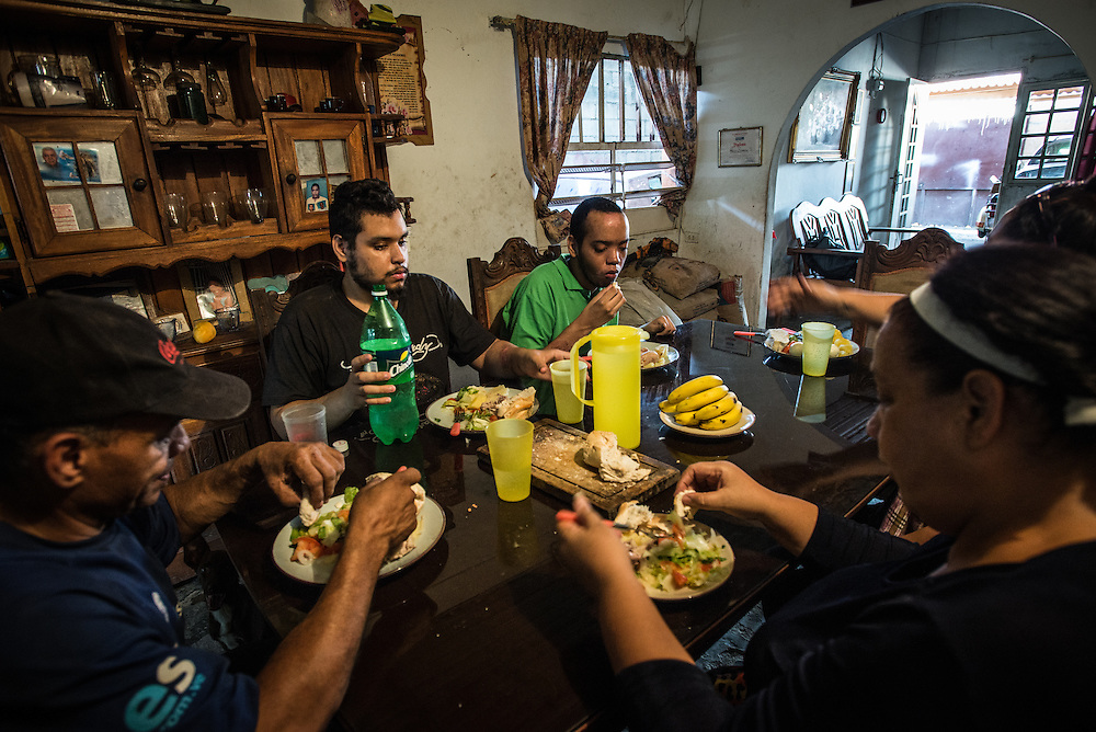 MARACAY, VENEZUELA - JULY 4, 2016: Mario Simeone and Evelin RodrÍguez eat lunch with their two schizophrenic sons, Gerardo and Accel.  The economic crisis that has left Venezuela with little hard currency has already hit its health system, leaving hospitals without antibiotics, surgeons without gloves and patients dying on emergency room tables.  But beyond the hospital wards, thousands more mental health patients—many of whom had been living relatively normal lives at home with their families under medication—are slipping back into relapse for lack of basic psychiatric medications which control their symptoms, medical experts say. PHOTO: Meridith Kohut for The New York Times