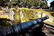A costumed re-enactors with a 17th century cannon along the fortifications of historic Charles Towne Landing, the original settlement of Charleston, SC where English settlers established the city in 1670. The site is now a state park and historic site.