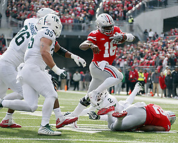 November 11, 2017 - Columbus, OH, USA - Ohio State Buckeyes quarterback J.T. Barrett (16) evades defenders Michigan State Spartans defensive end Jacub Panasiuk (96) and linebacker Joe Bachie (35) while running toward the end zone during the first quarter on Saturday, Nov. 11, 2017 at Ohio Stadium in Columbus, Ohio. (Credit Image: © Barbara J. Perenic/TNS via ZUMA Wire)