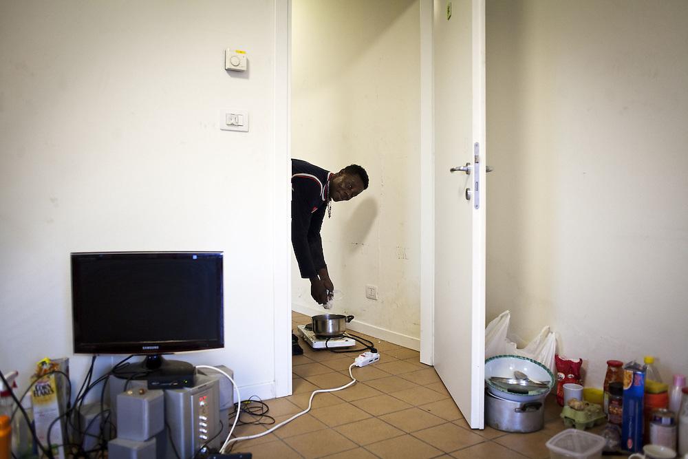 Un uomo cucina con una piastra elettrica. Iterno delle ex palazzine olimpiche.