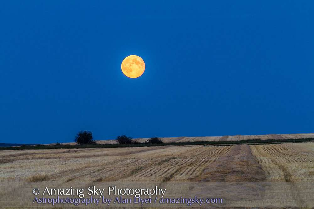 Moonrise a day after full, on Sept. 1, 2012 over swathed wheatfield. Taken from home with Canon 7D and 200mm lens. This is a single exposure.