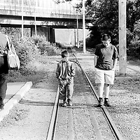 Waiting for the tram to go to school..Going to school can involve expenses families cannot afford like transport, books and clothes. Most families are ashame to send their children to school if not properly dressed...During the summer1999, over 245,000 Serbs and Roms fled to Serbia and Montenegro from or within Kosovo in fear of reprisals from the majority Albanian population, after NATO air strikes had forced the withdrawal of Yugoslav. In 2003, less than 2% of them had returned and a large number of these internally displaced persons (IDPs) were still living in camps in very difficult conditions..In addition, around 5,000 IDPs, mainly of Roma ethnicity, are living in unrecognized collective centres, makeshift huts, corrugated metal containers and other substandard shelters. .This work was meant to look at how the life of children and young adults is affected by the fact that they are IDPs. I asked myself more specifically what would be different for these children/young adults from the 'normal' people of their age as far as education, health,  social life, family, 'love' life and leisure are concerned. ..En attendant le tram pour aller à l'école..Envoyer ses enfants à l'école peut entrainer des frais supplémentaires pour la famille: frais de transport, livres de classe, vêtements. La plupart des familles ont honte d'envoyer leurs enfants à l'école si ceux-ci ne peuvent pas être bien habillés...Pendant l'été 1999, plus de 245 000 serbes et roms ont fuit le Kosovo pour chercher refuge en Serbie ou au Montenegro, par peur de représailles de la part de la majorité de la population albanaise après que les forces de l'OTAN aient forcé l'armée yougoslave à se retirer. En 2003, moins de 2% d'entre eux étaient rentrés chez eux et le plus grand nombre de ces 'déplacés' (IDPs) vivaient encore dans des centres d'accueil dans des conditions très difficiles..Environ 5 000 IDPs, la plupart romas, vivent dans des centres non reconnus faits de containers ou d'abris de fortune. .Ce