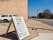 """26 APRIL 2020 - JEWELL, IOWA: Jewell, a small community in central IowA signboard advertising a grab and go meals being sold during a fund raiser in Jewell. Jewell, a small community in central Iowa, became a food desert when the only grocery store in town closed in 2019. It served four communities within a 20 mile radius of Jewell. Some of the town's residents are trying to reopen the store, they are selling shares to form a co-op, and they hold regular fund raisers. Sunday, they served 550 """"grab and go"""" pork roast dinners. They charged a free will donation for the dinners. Despite the state wide restriction on large gatherings because of the COVID-19 pandemic, the event drew hundreds of people, who stayed in their cars while volunteers wearing masks collected money and brought food out to them. Organizers say they've raised about $180,000 of their $225,000 goal and they hope to open the new grocery store before summer.      PHOTO BY JACK KURTZ"""
