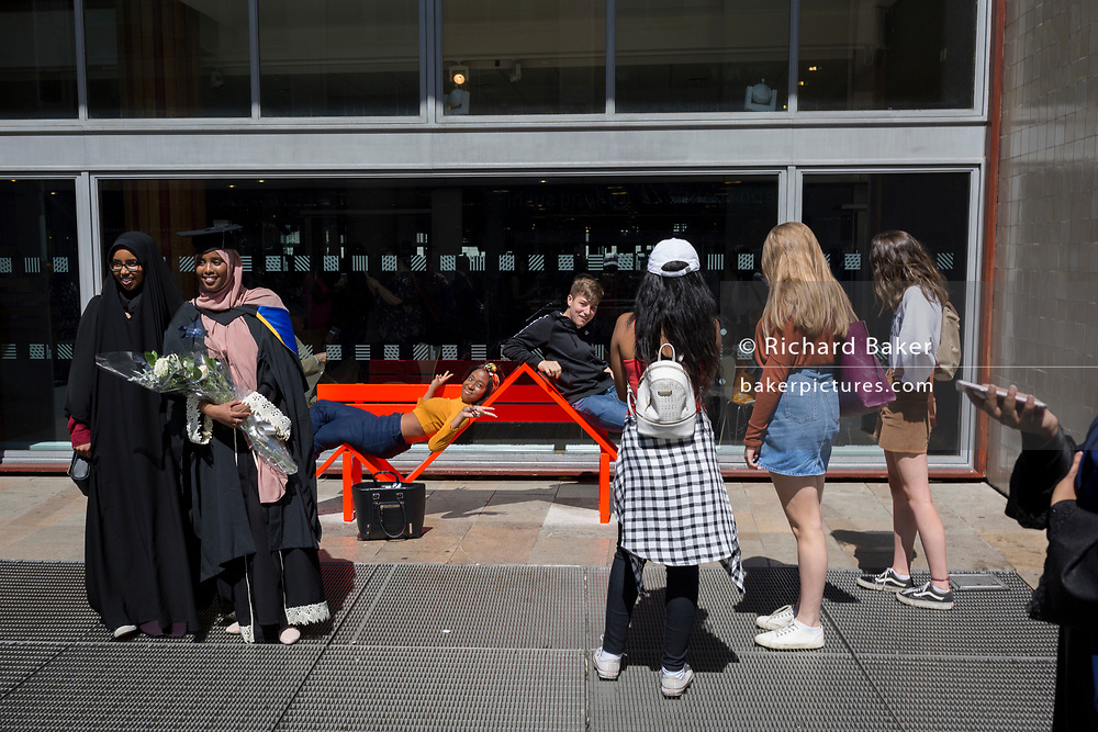 Mulsim graduates stand for a family photo wearing their rented gowns and mortarboard hats iafter their graduation eremony, in celebration of their university academic achievement, outside the Festival Hall, on 20th July 2017, on the Southbank, London, England.