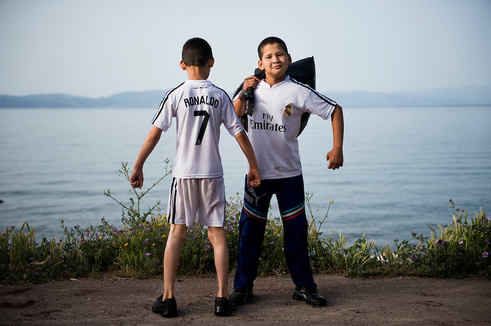 Two Afghan boys wearing Real Madrid t-shirts proud that made the journey to Greece posing minutes after their boat landed on the beach of Skala Sykaminias, Lesbos island, Greece.Everyday hundreds of refugees, mainly from Syria and Afghanistan, are crossing in small overcrowded inflatable boats the 6 mile channel from the Turkish coast to the island of Lesbos in Greece. Many spend their life savings, over $1000, to buy a space on those boats.