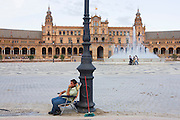 With his brush at the ready, a donkey ride owner awaits new business during the quiet Siesta afternoon period in Seville's Plaza de Espana. This semicircular enclosure was built by Aníbal González, the great architect of Sevillian regionalism, for the Ibero-American exposition held in 1929. Today the Plaza de España mainly consists of Government buildings. The Seville Town Hall, with sensitive adaptive redesign, is located within it. The Plaza's tiled 'Alcoves of the Provinces' are backdrops for visitors portrait photographs, taken in their own home province's alcove.
