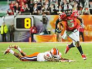 January 3, 2014 - Miami Gardens, Florida, U.S: Ohio State Buckeyes quarterback Braxton Miller (5) avoids a Clemson Tigers defender during the Discover Orange Bowl between the Clemson Tigers and the Ohio State Buckeyes at Sun Life Stadium in Miami Gardens, Fl
