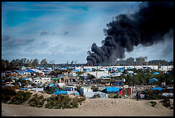 October 27, 2016 - Calais, Northern France, France - Image ©Licensed to i-Images Picture Agency. 27/10/2016. Calais, France. Calais Jungle Migrant Camp. Fires still burning among the remains of  the migrant camp as Refugees leave the Calais Jungle migrant camp the day after it caught fire and the French police closed it down. Picture by Andrew Parsons / i-Images (Credit Image: © Andrew Parsons/i-Images via ZUMA Wire)