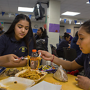 WASHINGTON, DC - DEC 16: Dinia Lovo Marquez, an 18-year-old senior at Bell Multicultural High School eats lunch with Jocelyn Cruz, 17 (right), December 16, 2013, in Washington, DC. Dinia, an immigrant from El Salvador, works as a janitor at the Department of Education after school, and wants to be the first in her family to attend college. (Photo by Evelyn Hockstein/For The Washington Post)