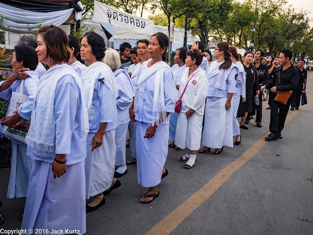 22 NOVEMBER 2016 - BANGKOK, THAILAND:  Women dressed in white Buddhist mourning clothes wait to enter Sanam Luang in Bangkok. Hundreds of thousands of Thais gathered across Thailand Tuesday to swear allegiance to the Chakri Dynasty, in a ceremony called Ruam Phalang Haeng Kwam Phakdi (the United Force of Allegiance). At Sanam Luang, the Royal Parade Ground, and location of most of the mourning ceremonies for the late King, people paused to honor His Majesty by singing the Thai national anthem and the royal anthem.      PHOTO BY JACK KURTZ