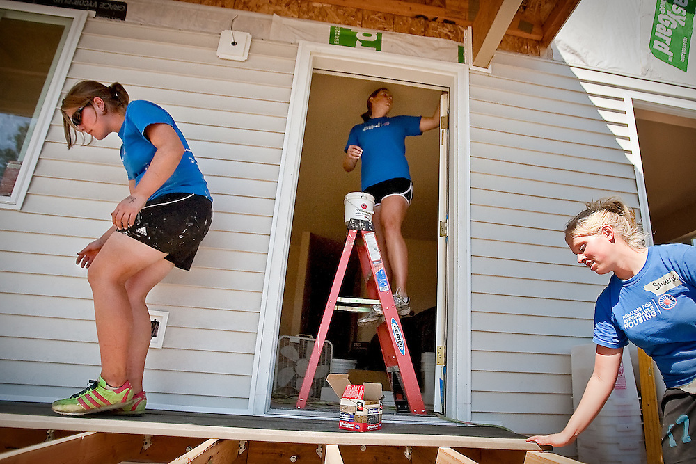 JEROME A. POLLOS/Press..Beth Haley, left, and Suzanne Willis work on constructing a deck outside a Habitat for Humanity home in Post Falls as Caroline Godfrey paints a living room inside Monday. More than 30 volunteers from the Bike & Build program helped with work on the home as part of their cross-country trek to help work on affordable house projects.
