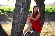 Teen in red dress sits in tree