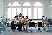 Four business people using laptop in office