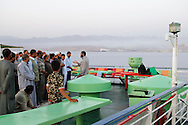 A man on a ferry traveling from Nuweiba, Egypt to Aqaba, Jordan preaches to fellow Muslim passengers before they perform sunset prayers together. Most of the passengers are Egyptians on their way to jobs in other Arab countries. The man preaching is an Egyptian on his way to Saudi Arabia (via Aqaba) to undertake further religious study. The land in the distance is the outskirts of Aqaba, Jordan.