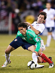 United States forward Clint Dempsey (8) gets tangled with Mexico midfielder Israel Martinez (14).  The United States men's soccer team defeated the Mexican national team 2-0 in CONCACAF final group qualifying for the 2010 World Cup at Columbus Crew Stadium in Columbus, Ohio on February 11, 2009.