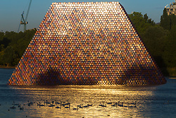 Shimmering in the evening sunshine and reflected on the ripples as swans and geese cross the reflection on the water, artist Christo's 'Mastaba' is an installation made up of over 7,000 barrels floating on The Serpentine in London's Hyde Pak. London, July 02 2018.