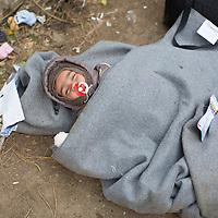 SERBIEN, Grenzstadt Berkasovo, Stadtgebiet von Šid. 08.10.2015 / Fluechtlinge an der serbisch-kroatischen Grenze: Ein Baby liegt warm eingewickelt am Wegesrand, unmittelbar an der illegalen Grenze von Serbien zu Kroatien. Die Mutter ist noch verzweifelt auf der Suche nach Babynahrung, bevor der Fussmarsch weitergeht. Die kroatische Grenze, und damit die EU-Aussengrenze, ist nur noch 100 Meter entfernt.