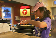 Megan Terukina of Cedar Rapids works on measuring out cheese for pizzas at Tomaso's Pizza, 3234 Center Point Road NE in Cedar Rapids on Thursday, December 27, 2012.