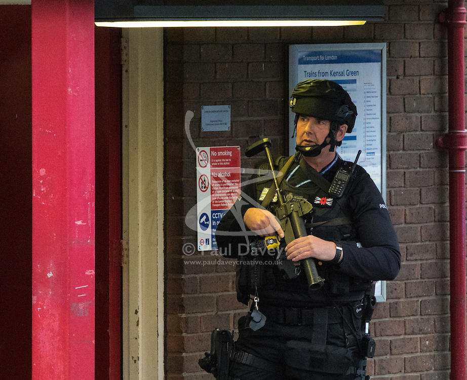 """Kensal Green, London, May 31st 2016. Police in body armoured protective headgear seal off Kensal Green tube station in North West London in what is described as a """"security incident"""". PICTURED: An armed officer outside the station entrance."""